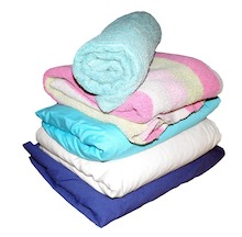 This is a photo of folded linens and towels and is used to illustrate laundry on the energy savings checklist.